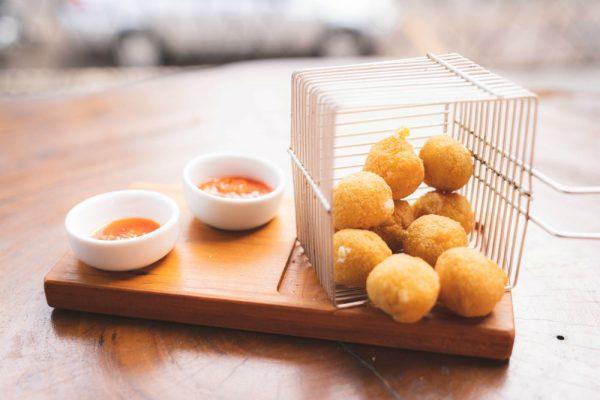 Experimente a bolinha de queijo, crocante e deliciosa, acompanhada de pimenta de boteco.
